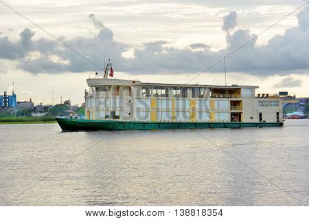 IQUITOS, PERU - OCTOBER 13, 2015: The Amazon Discovery river cruise ship. Crew on the deck with Iquitos in the Background.