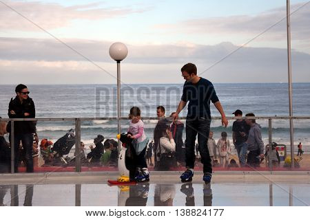Sydney Australia - Jul 17 2016. A little girl and her father are ice skating on Bondi ice rink. Australia's only beachside ice rink is on Bondi beach.