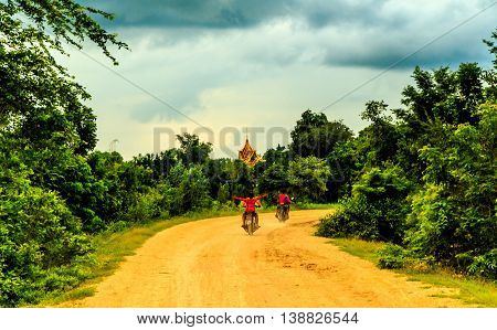 Kids ride a motorbike down a dirt road towards a golden temple in the green Cambodian countryside