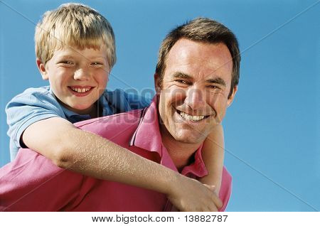 Father giving son piggyback ride outdoors smiling