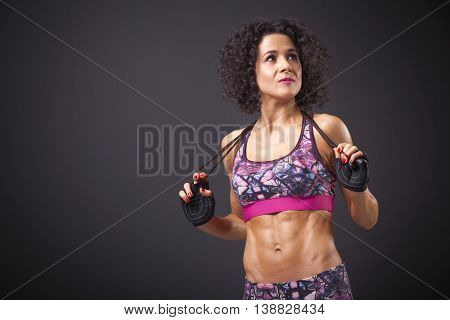 Pretty fitness woman posing with a jumping rope on black background
