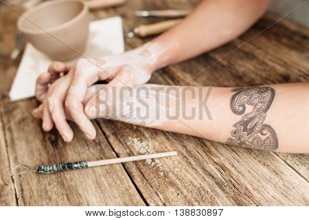 Dirty hands of potter lying next to art tools on wooden table. Tired artisan. Absence of inspiration, lost talent, artisan in depression
