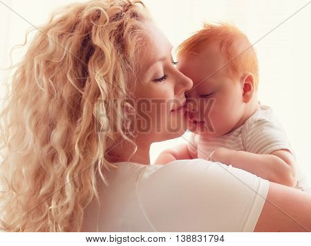 portrait of young mother cherishes her infant baby poster