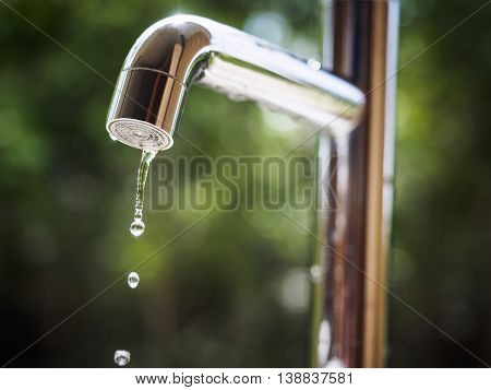 Water tap with water drop Blur outdoor Green park background