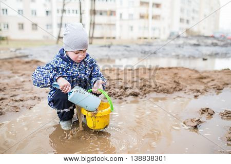 Boy Playing In A Muddy Puddle