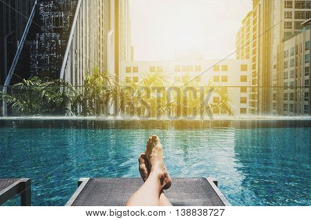 Relaxing in holidays, Asian guys feet on sun bathing bed at roof top swimming pool in the city