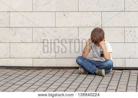 Sad, lonely, unhappy, upsed, disappointed tired child sitting alone on the ground Outdoor
