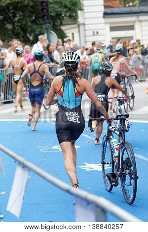 STOCKHOLM - JUL 02 2016: Triathlete Claire Michel e running with cycle in the transition zone in the Women's ITU World Triathlon series event July 02 2016 in Stockholm Sweden