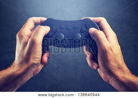 Man using game pad controller to play entertaining electronics video games gaming and entertainment concept poster