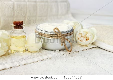 Rose spa products. Facial cream container, fresh beige garden roses, aroma essential oil, white towel.