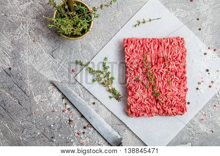 Minced meat on paper with seasoning and fresh thyme on gray background, top view