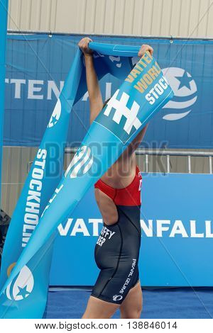 STOCKHOLM - JUL 02 2016: Winning triathlete Flora Duffy (BER) lifting the finishing tape at the finish in the Women's ITU World Triathlon series event July 02 2016 in Stockholm Sweden