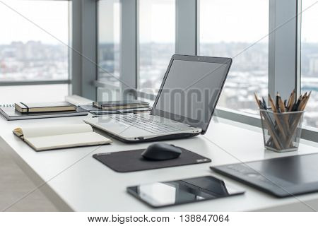Workplace with notebook laptop Comfortable work table in office with windows and city view