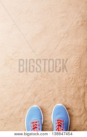 Blue sports shoes with pink shoelaces laid on sand beach background, studio shot, flat lay. Copy space.