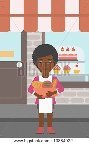 An african-american young female baker holding basket with bakery products. Female baker standing in front of bakery. Baker with bowl full of bread. Vector flat design illustration. Vertical layout.