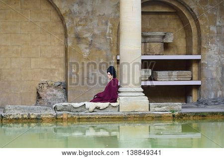 Bath Somerset United Kingdom - June 30 2016: Woman in Roman costume next to pillar recreating scene at the Roman Baths in centre of city