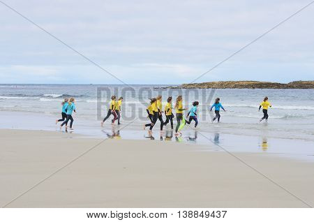 Sennen Cove Cornwall United Kingdom - July 02 2016: Group of young children running out to sea for surfing lesson