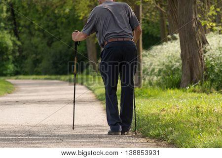 frail man walking with difficulty with walking sticks