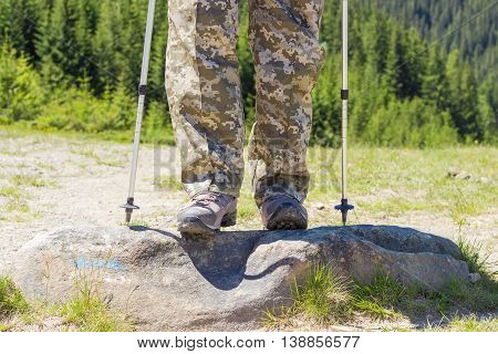 Hiker legs in trousers color of digital camouflage and hiking boots and the lower part of the trekking poles closeup on the background of a mountain with fir forest