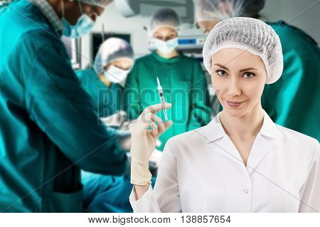 Young female anesthetist with syringe on the surgery teem background