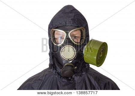 Head and shoulders of a person in a rubber gas mask with filter mounted on side of the mask and drinking tube and in a black jacket with a hood on a light background