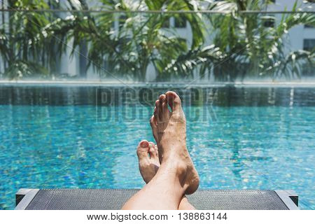 Sunbathing at swimming pool at tropical resort in summer, Asian guy feet lying down on sunlounger at pool side