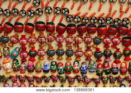 Russia Moscow - June 24 2015: Colorful russian souvenirs (dolls Matryoshka caviar samovar scrambled eggs in a frying pan porridge in a pot) in the form of magnets at market on the Arbat