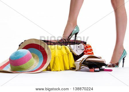 Girl's leg on filled suitcase. Hat near closed filled suitcase. Luggage for trip is ready. Never too much clothing.
