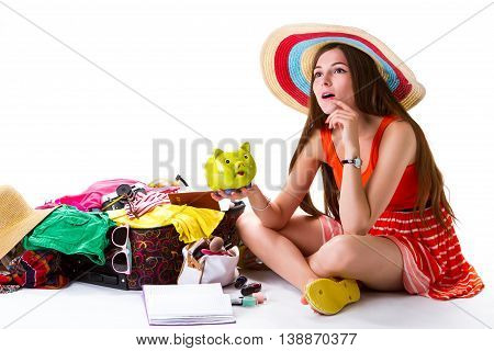 Girl sits beside overfilled suitcase. Lady with green money box. Best idea for vacation. Need some time to think.