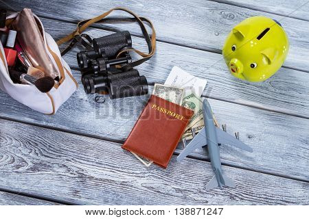 Passport and a toy plane. Lime piggy bank and binoculars. Run away from the bustle. Take a vacation this summer.