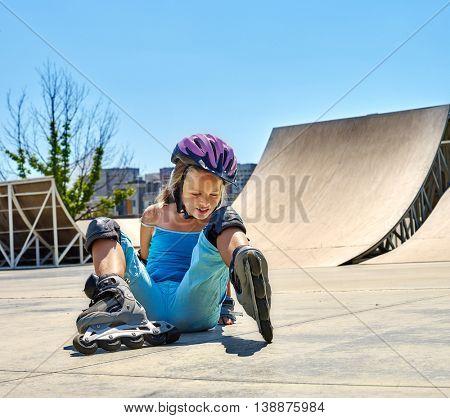 Child riding on roller skates in skatepark. Child roller fall down in roller skates.