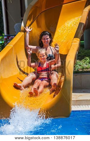 Happy family with child on water slide at aquapark hands up. Water slides with flowing water in aqua park. Mother and daughter. Summer water park holiday. Outdoor.