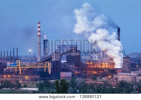 Metallurgical plant with white smoke at night. Steel factory with smokestacks . Steelworks iron works. Heavy industry. Air pollution from smokestacks ecology problems. Industrial landscape at twilight