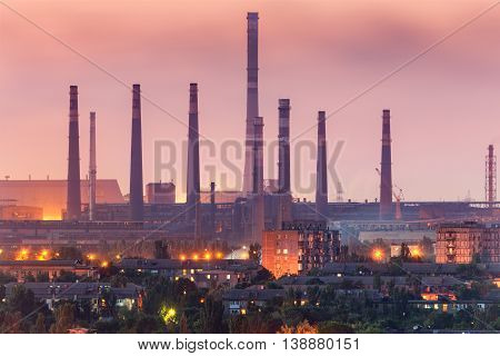 City buildings on the background of steel factory with smokestacks at night. Metallurgical plant with chimney. steelworks iron works. Heavy industry. Air pollution smog. Industrial landscape