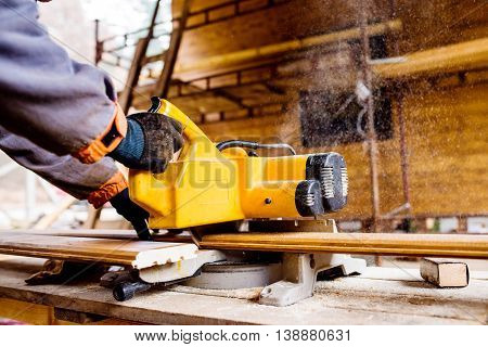 Hands of unrecognizable carpenter working. Man using circular saw to cut planks of wood for home construction