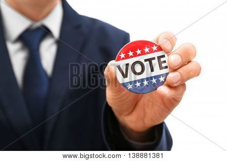 American votes concept. Man holding voting badge, close up