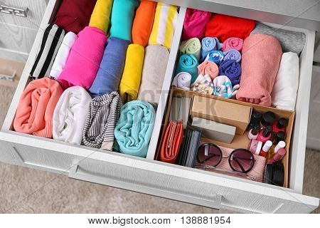 Neatly folded clothes with accessories in chest of drawers poster