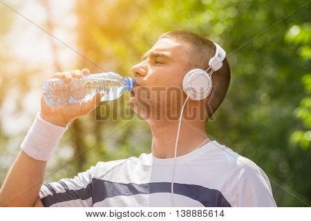 Portrait of thirsty sportsman with headphones drinking water from the plastic bottle in the park during the sunny day. Ideal for bottle pack shoot adding. Sport, fitness, nature and healthy lifestyle concepts.