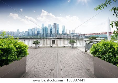 cityscape and skyline of downtown near bridge of chongqing in sunny cloud sky on view from empty wood floor