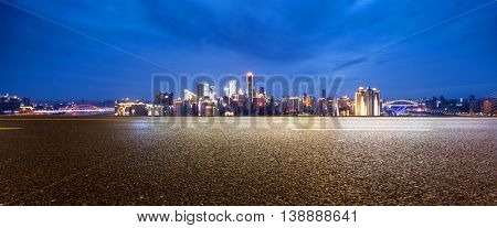 cityscape and skyline of chongqing at twilight on view from empty asphalt road
