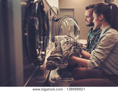 Young cheerful couple doing laundry together at laundromat shop.