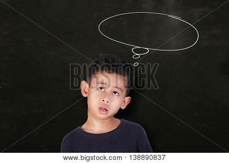 Portrait of Asian little boy looking up and thinking something over blackboard with empty dreaming speech bubble drawn above his head