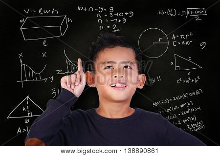 Portrait of little Asian student boy smiling and raise his pointing finger up get an idea to solve math problem over blackboard with mathematic schemes doodle drawn on it