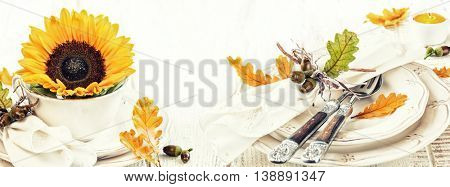 Table setting decoration for autumn holiday with flower and leaves