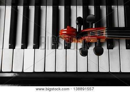 Violin neck lying on piano keys, close up