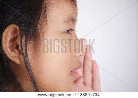 closeup portrait of beautiful little Asian girl whispering carefully with her hand covering her lips from side gesture trying to say secretly interesting information conversation news