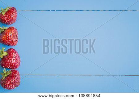Fresh strawberries in a line on blue wooden background, copyspase