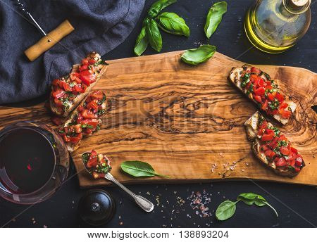 Tomato and basil bruschetta with glass of red wine served with olive oil, salt and fresh herbs on olive wooden board over black background, top view, copy space, horizontal composition