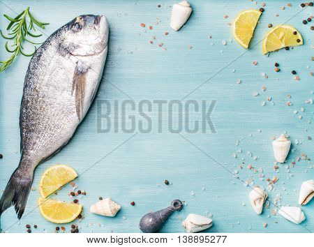 Fresh raw sea bream fish decorated with lemon slices, spices and sea shells on blue wooden background. Healthy food concept, top view, copy space