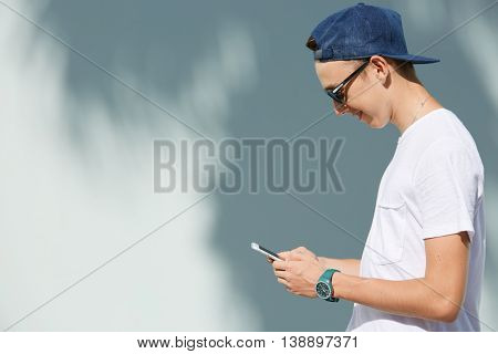 Profile Of Smiling High School Student Boy Wearing Shades And Snapback Holding Mobile Phone, Messagi